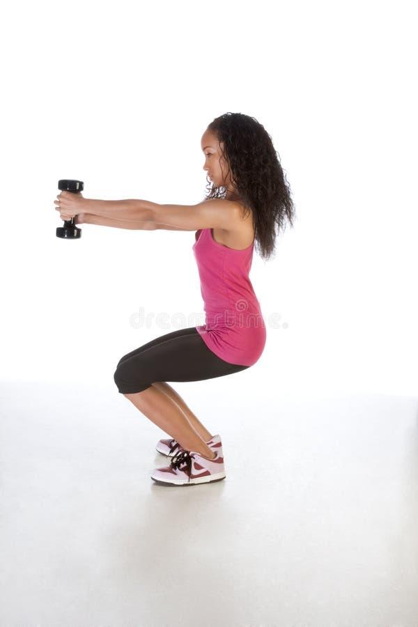 Femme ethnique mince établissant avec l'haltère noir photographie stock