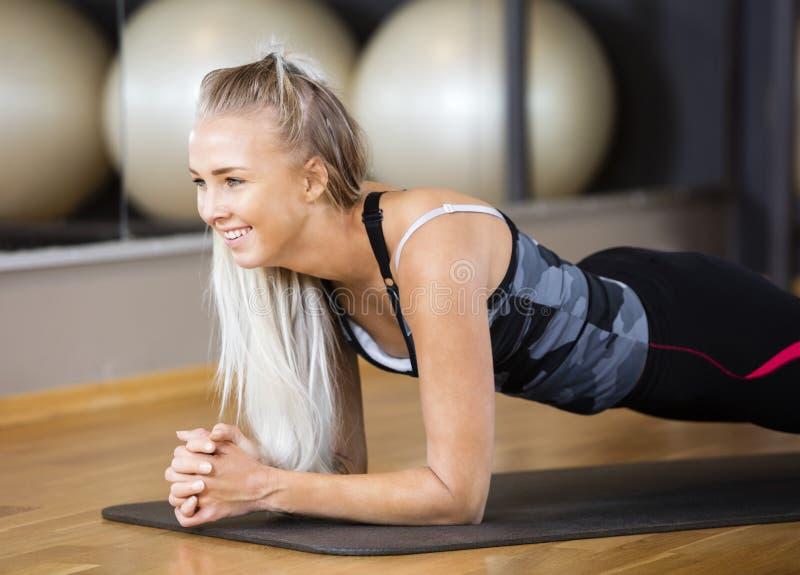 Femme exécutant l'exercice de planche dans le gymnase photos stock