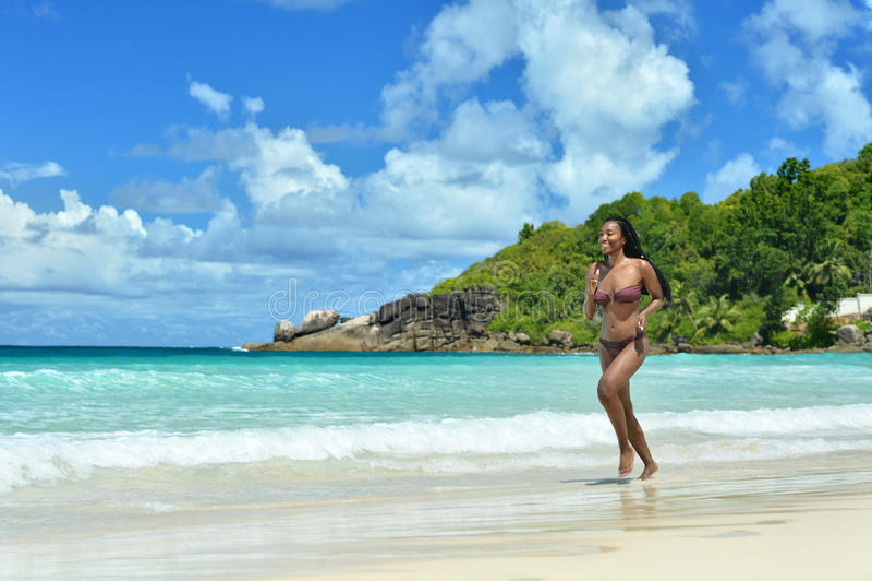 Femme exécutant le long de la plage image stock