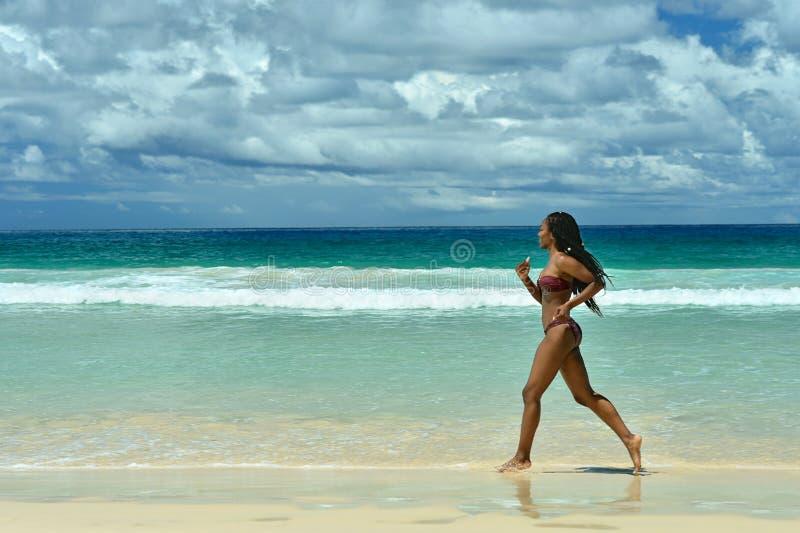 Femme exécutant le long de la plage photo libre de droits