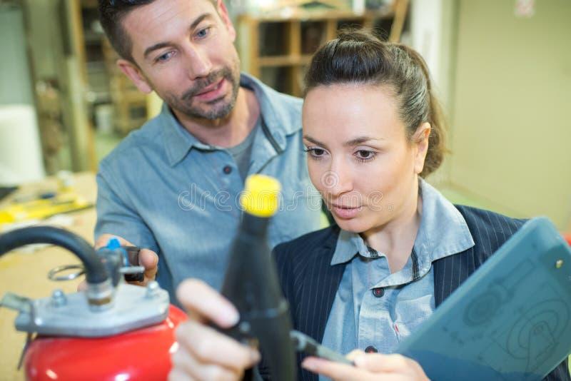 Femme examinant le produit de réservoir sous pression images stock
