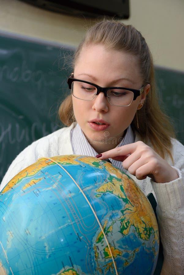 Femme examinant un globe photo stock