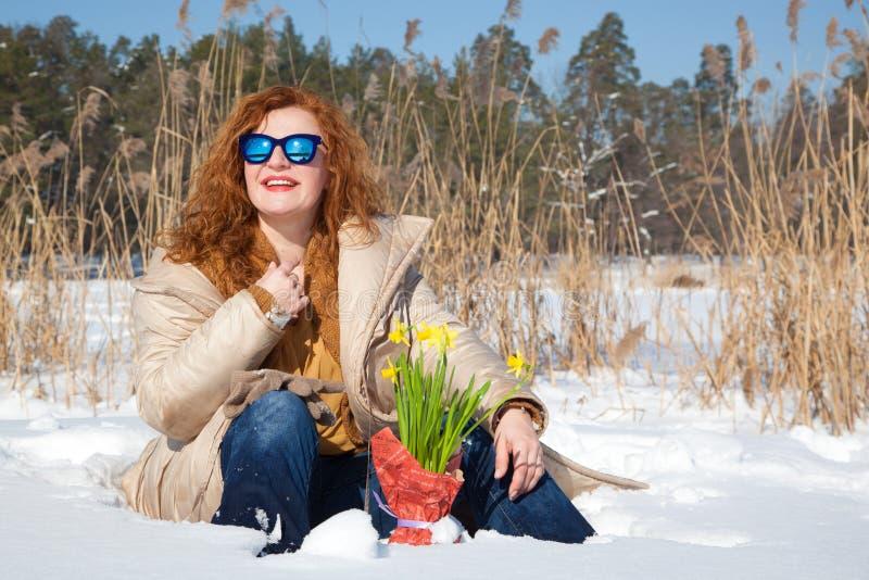 Femme excellente positive appréciant le jour d'hiver tout en se reposant en congère contre la nature rurale photos libres de droits