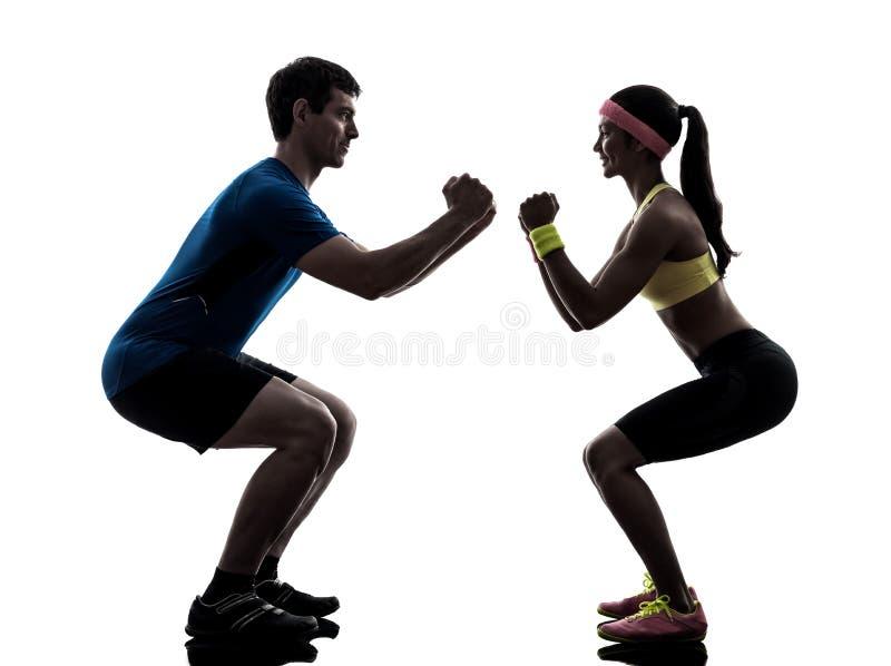Femme exerçant la séance d'entraînement de forme physique avec la silhouette d'entraîneur de l'homme photos libres de droits