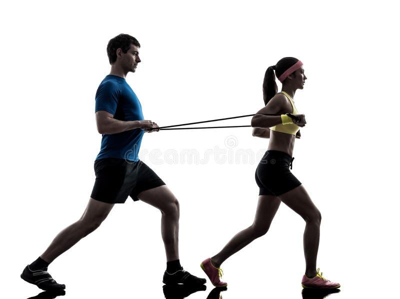 Femme exerçant une bande élastique de résistance de forme physique avec l'entraîneur de l'homme images libres de droits