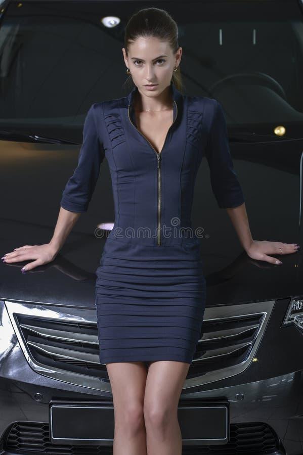 Femme expressive magnifique de yeux se penchant contre sa voiture image libre de droits