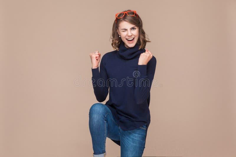 Femme expressive réussie se réjouissant sa victoire photographie stock libre de droits