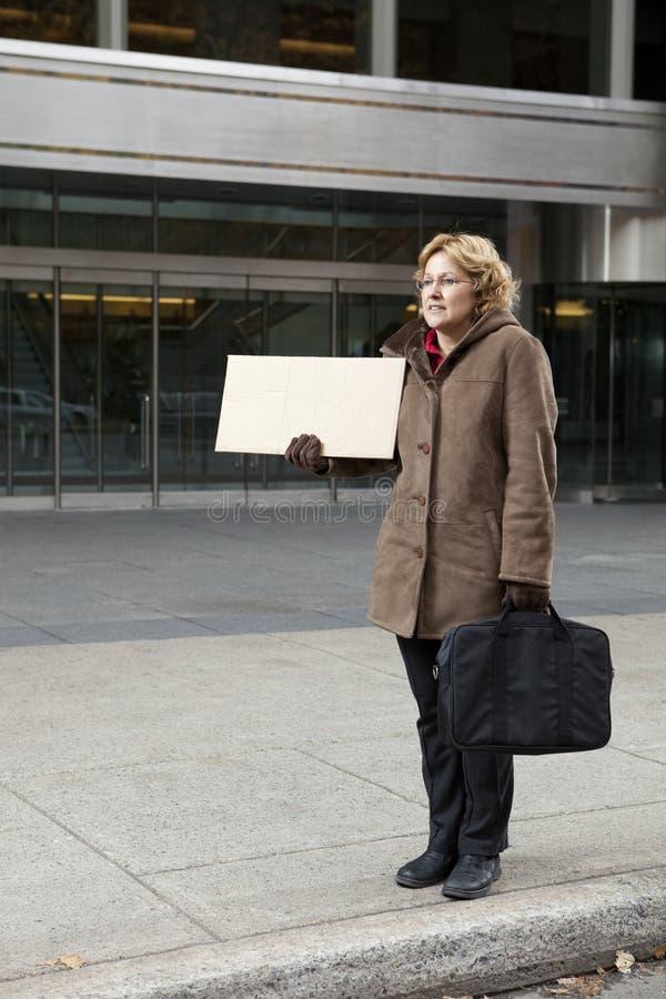 Femme extérieur d'affaires avec la verticale blanc de signe images stock