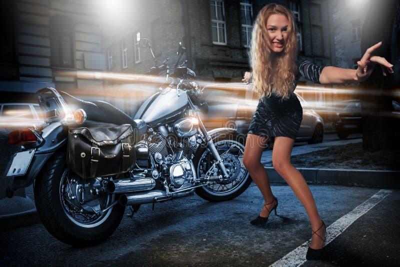 Femme extrême folle avec sa motocyclette dehors à la rue de nuit photographie stock