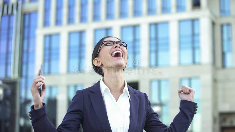 Femme extrêmement heureuse dans nouvelles de lecture de costume de bonnes, employé de bureau obtenant la promotion photo stock