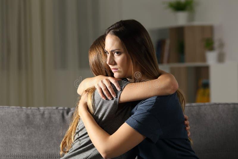 Femme fâchée étreignant un ami à la maison photographie stock