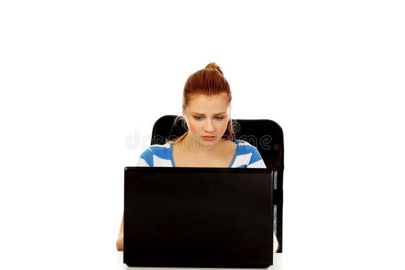 Femme fâchée adolescente avec l'ordinateur portable se reposant derrière le bureau photos libres de droits