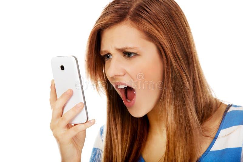 Femme fâchée adolescente criant dans le téléphone photos libres de droits