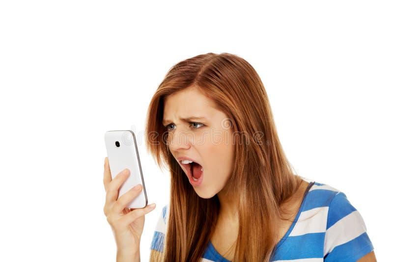 Femme fâchée adolescente criant dans le téléphone photo stock