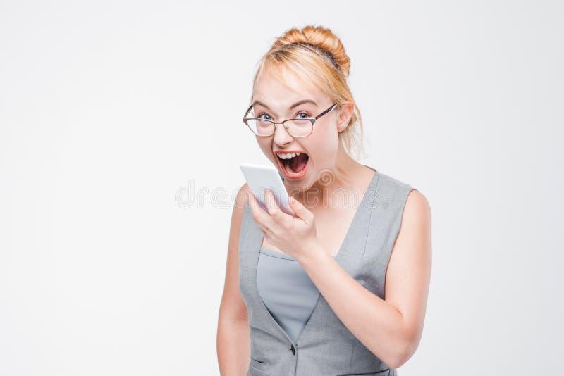 Femme fâchée avec le téléphone furieux, exaspéré et fou photographie stock