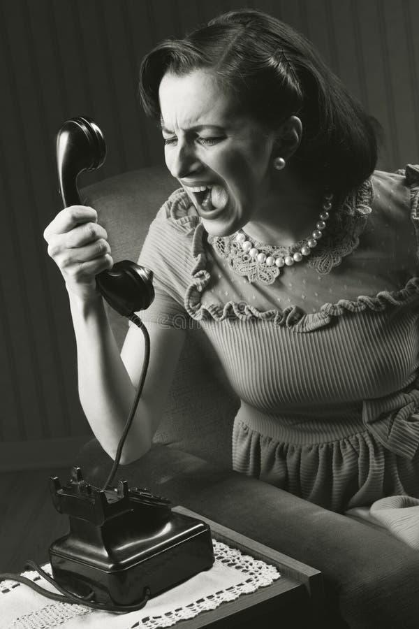 Femme fâchée criant au rétro téléphone images stock