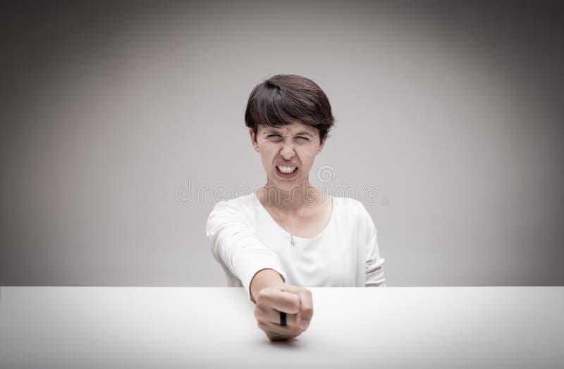 Femme fâchée frappant son poing sur la table photos stock
