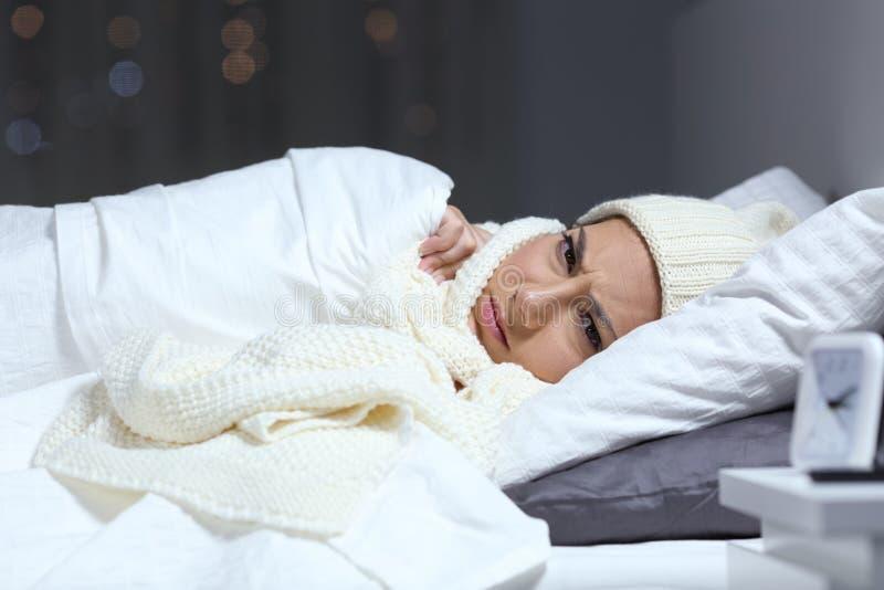 Femme fâchée maintenant chaude dans le lit en hiver froid photos libres de droits