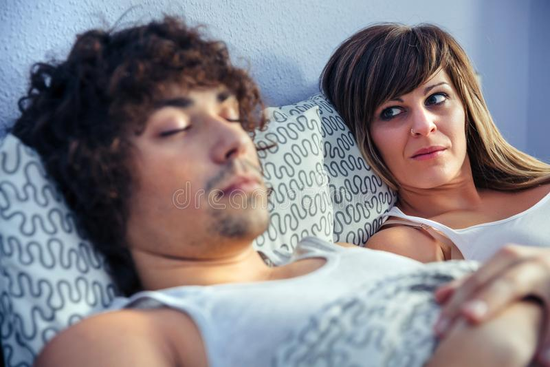 Femme fâchée regardant au sommeil de jeune homme photo stock