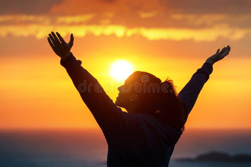 Femme félicitant et appréciant le coucher du soleil d'or photo stock