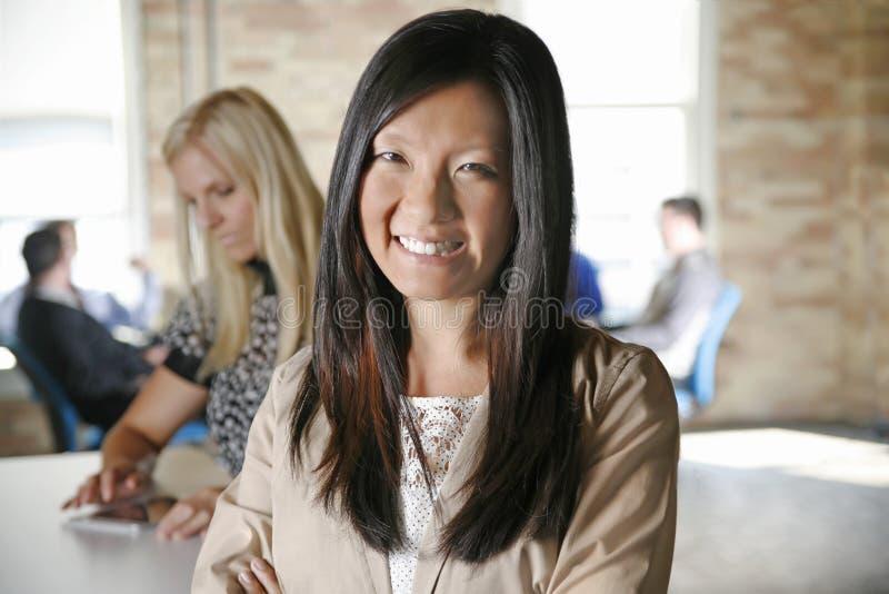 Femme féminine asiatique d'affaires avec l'équipe à l'arrière-plan moderne de bureau photo libre de droits