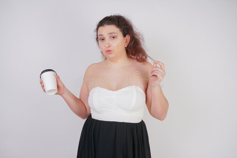 Femme féminine avec le corps plus de taille dans une robe à la mode tenant une tasse de café de papier et posant sur un fond b images stock