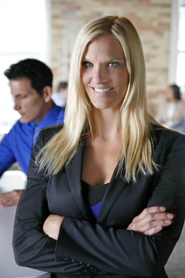 Femme féminine blonde d'affaires souriant devant l'équipe dans le bureau urbain de brique photos stock