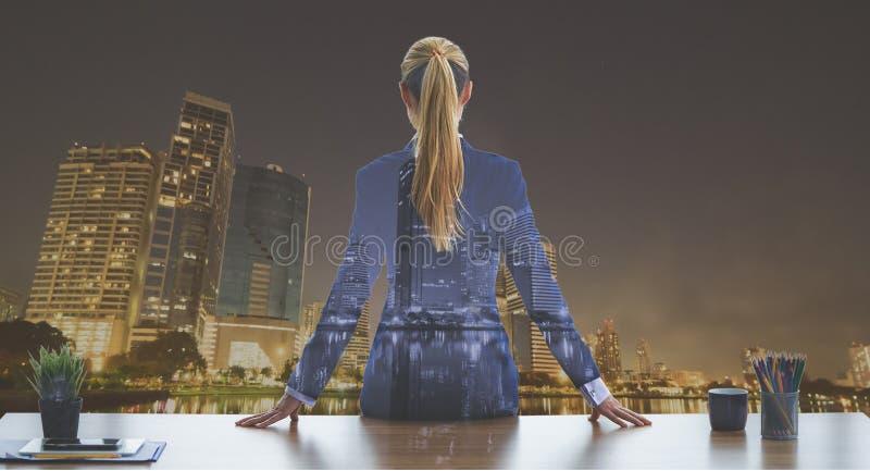 Femme féminine d'affaires regardant les fenêtres de ville de nuit pour photo stock