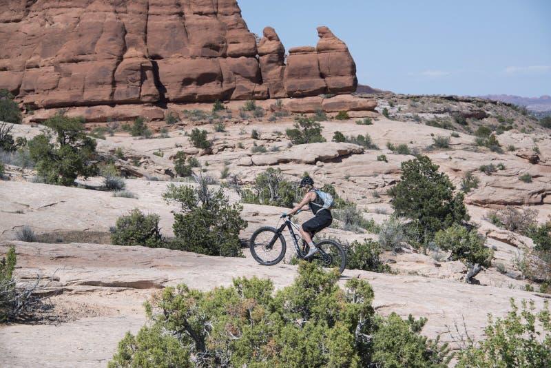 Femme féminine de cycliste de montagne montant son gros vélo de pneu sur le slickrock dans Moab Utah photos stock