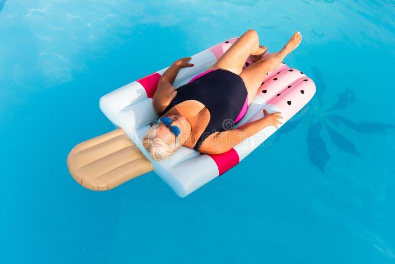 Femme féminine supérieure avec des mensonges lumineux en verre de soleil sur un flotteur formé par glace gonflable de piscine photos stock