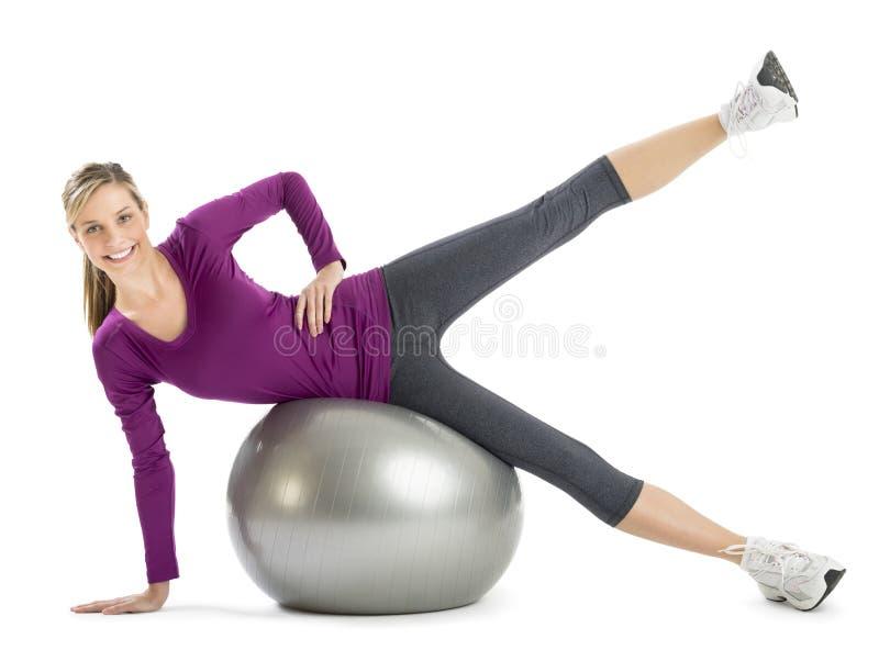 Femme faisant étirant l'exercice sur la boule de forme physique image libre de droits