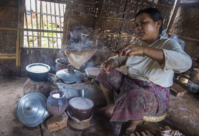 Femme faisant cuire des crêpes birmannes traditionnelles image stock