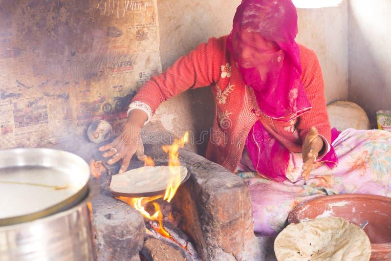 Femme faisant cuire le chapati images stock