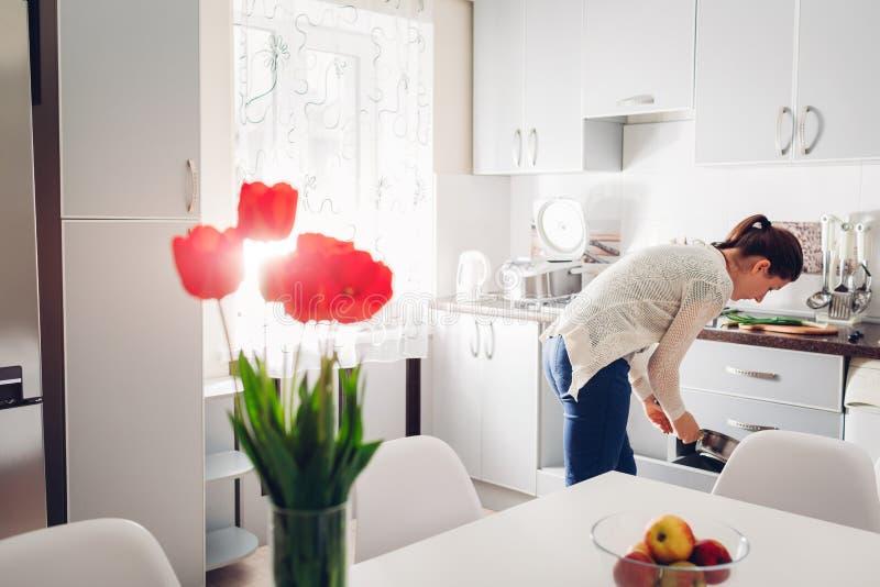 Femme faisant cuire le dîner dans la cuisine Jeune fille prenant la casserole Conception moderne de cuisine images libres de droits