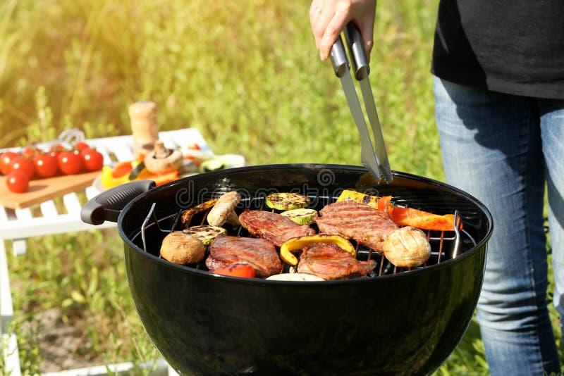 Femme faisant cuire les bifteks et les légumes savoureux image stock