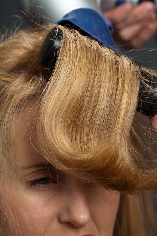 Femme faisant dénommer le cheveu images stock