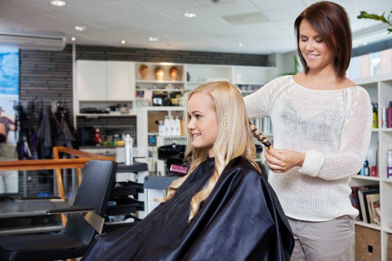 Femme faisant dénommer ses cheveux images stock