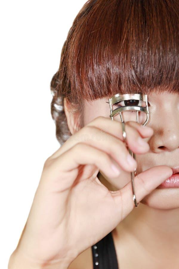 Femme faisant des cils de boucle utilisant courber l'outil cosmétique photographie stock