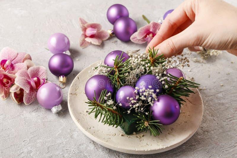 Femme faisant des décorations de Noël avec les boules violettes, sapin et ou photographie stock