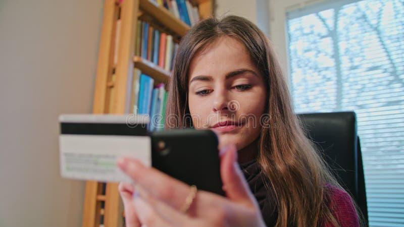 Femme faisant des emplettes en ligne avec la carte de crédit utilisant le téléphone photographie stock