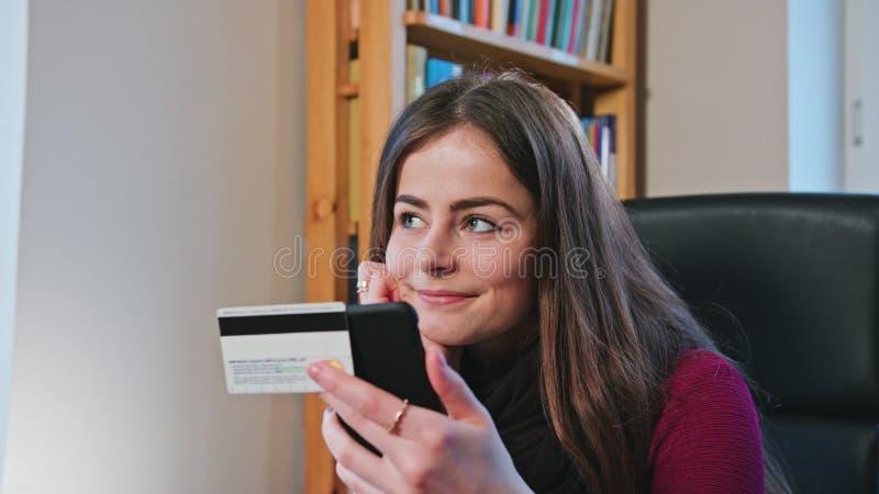 Femme faisant des emplettes en ligne avec la carte de crédit utilisant le téléphone images stock