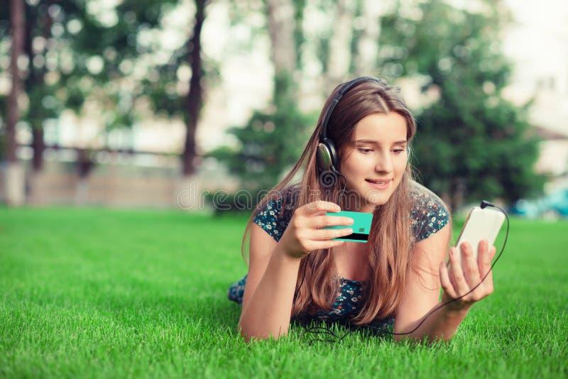 Femme faisant des emplettes en ligne avec une carte de crédit et un téléphone avec des écouteurs dehors photo libre de droits