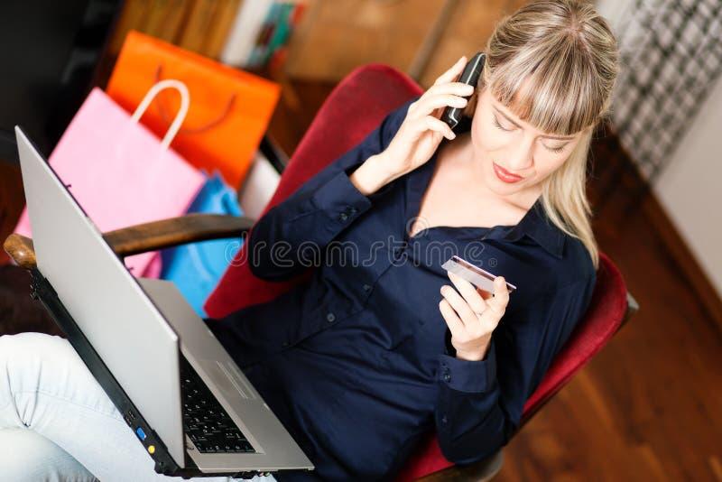 Femme faisant des emplettes en ligne par l'intermédiaire de l'Internet de la maison photographie stock