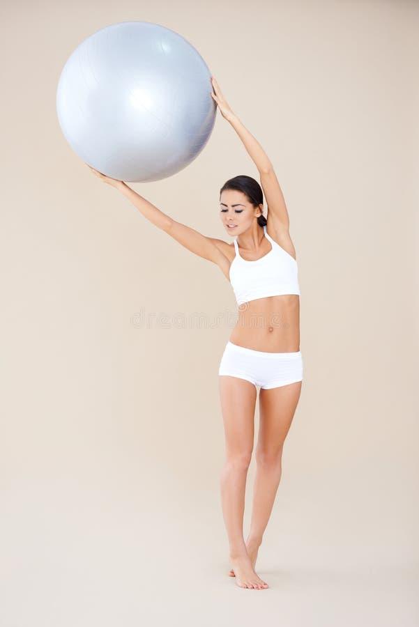 Femme faisant des exercices avec la bille de forme physique photos stock