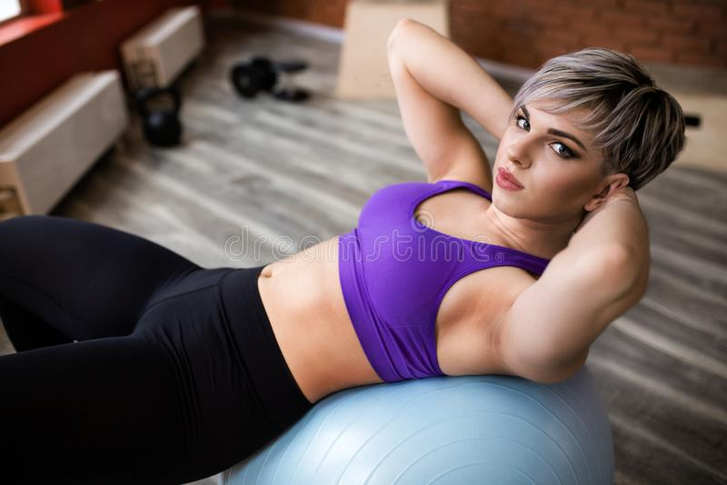 Femme faisant des exercices avec le fitball dans la classe de gymnase de forme physique Muscles abdominaux s'engageants de noyau  photo libre de droits