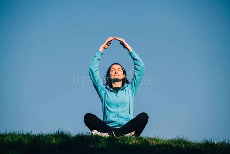 Femme faisant des exercices de relaxation en parc photo stock