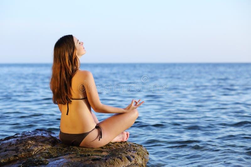 Femme faisant des exercices de yoga sur la plage photos libres de droits