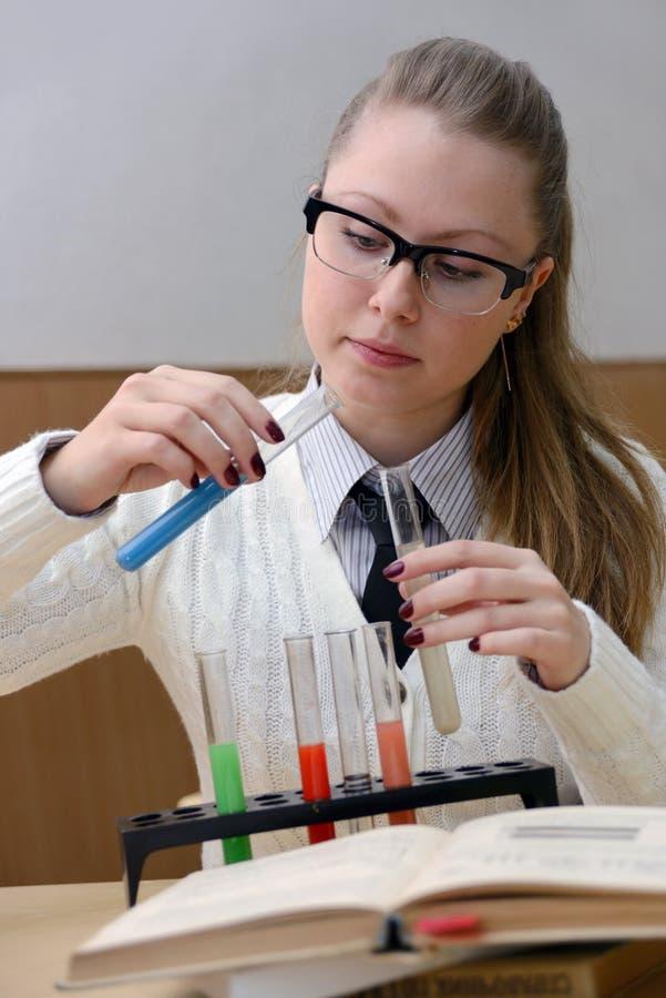 Femme faisant des expériences en chimie photos stock
