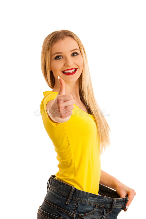Femme faisant des gestes le succès comme elle a perdu le poids portant trous trop grand image stock