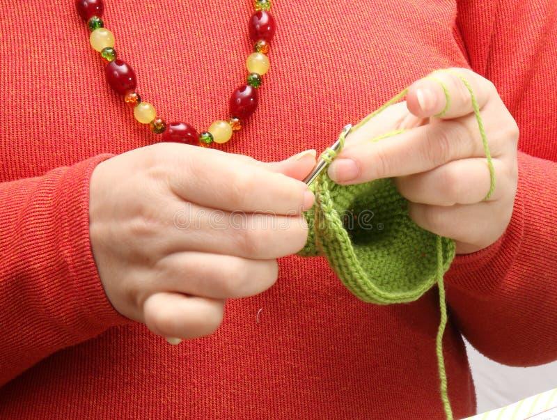 Femme faisant du crochet avec le fil vert photos stock
